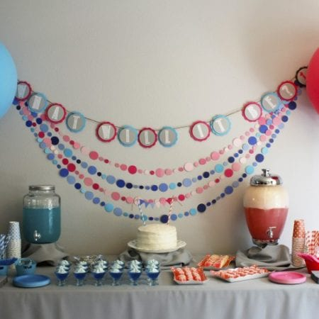 Pink and blue banners, drinks, plates, cups and foods image.