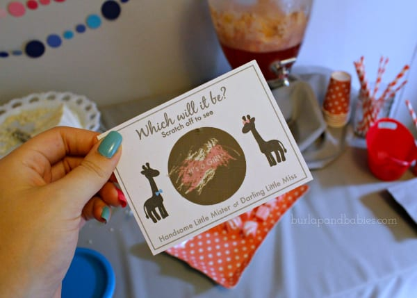 Hand holding a gender reveal scratch off card image.