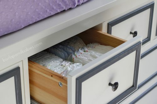 White dresser with gray accent with a drawer open image.