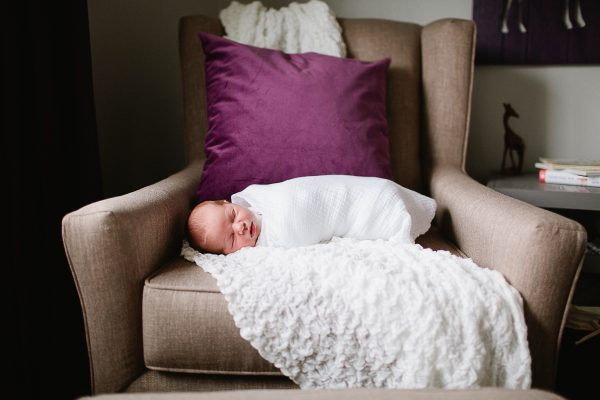 Swaddled baby girl sleep in chair with purple pillow.