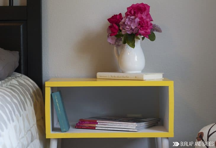 Yellow side table with vase of flowers on top image.