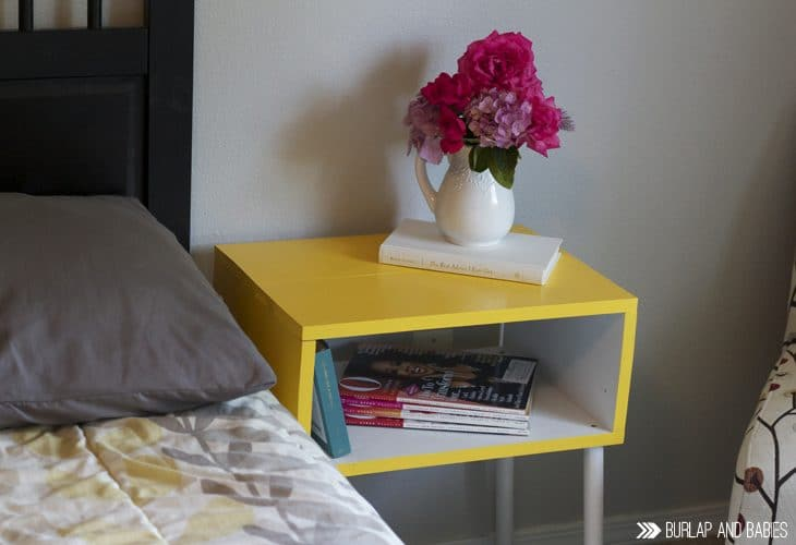 Yellow side table next to a bed with pink flowers in a vase on top image.