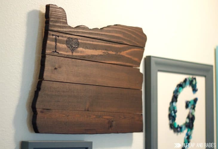 Rustic wooden wall art in the shape of a state image.