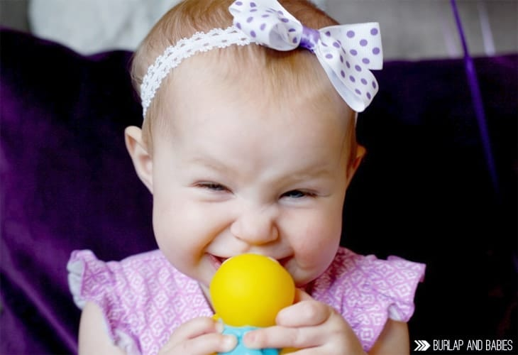 Little baby girl smiling with yellow toy image.