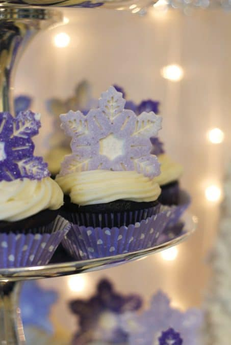 Cupackes with purple snowflake toppers.