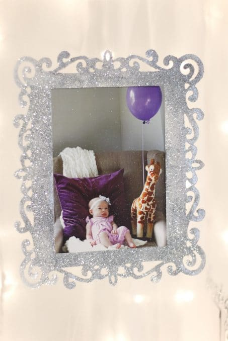 Frame covered in silver glitter featuring a picture of a baby girl and purple balloons image.
