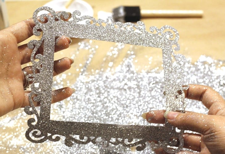 Hands showing frame covered in glued on silver glitter image.