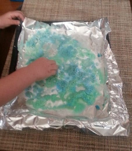 Little hands doing a science project with foil image.