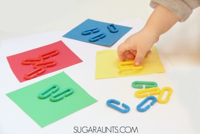Child's hand matching objects with the right color image.