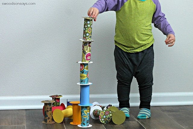 Little boy playing with toilet paper rolls as blocks image.