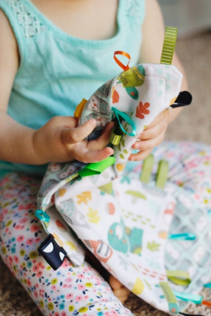 Little girl holding a tag blanket image.