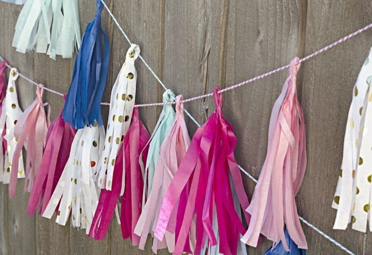 Pink, white, gold, blue tassels tied to a fence wall image.