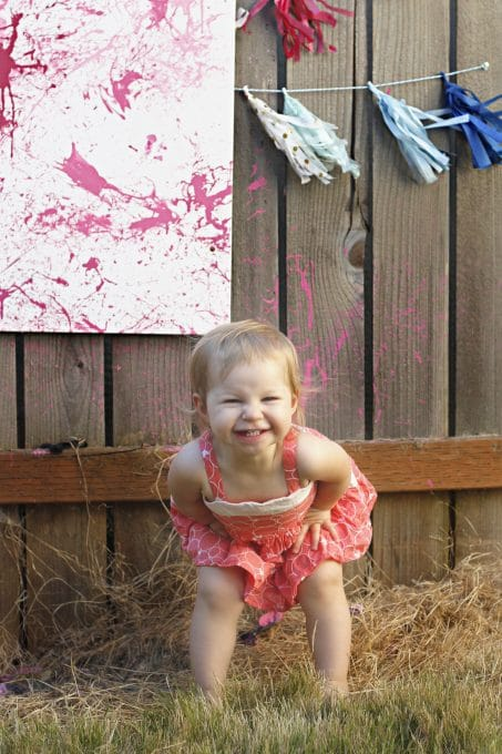 Smiling little girl in front of wall with white canvas splattered in pink paint image.
