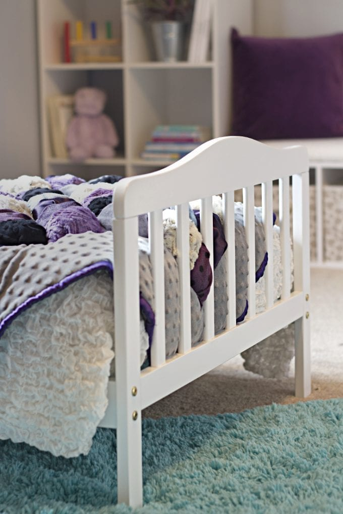 Toddler white bed frame with purple quilt image.