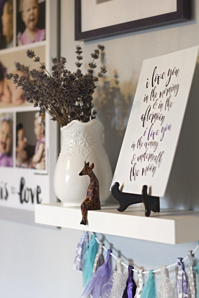 Floating shelf with a quote, a vase, and a giraffe image.