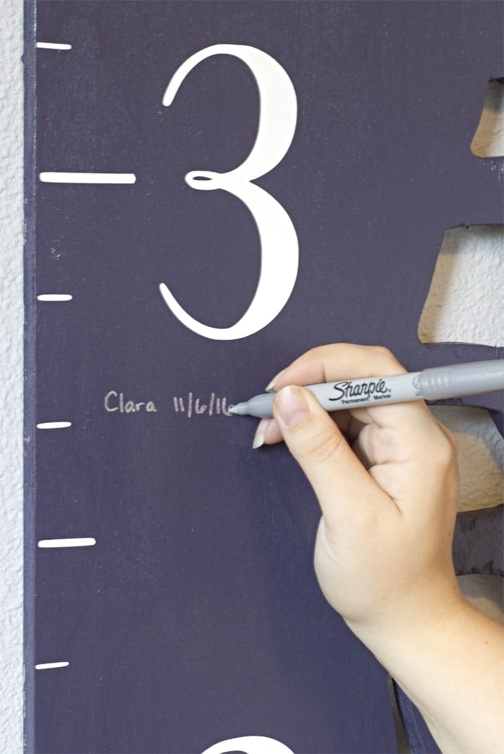 Hand writing a name and height on growth chart image.