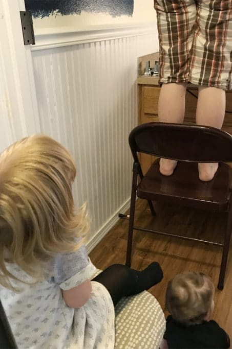 Person standing on a chair painting a wall image.
