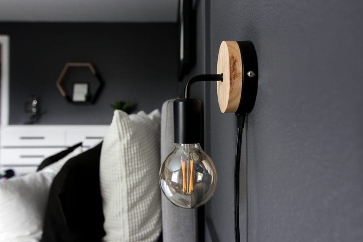 Minimalist wall sconce above nightstand in modern bedroom