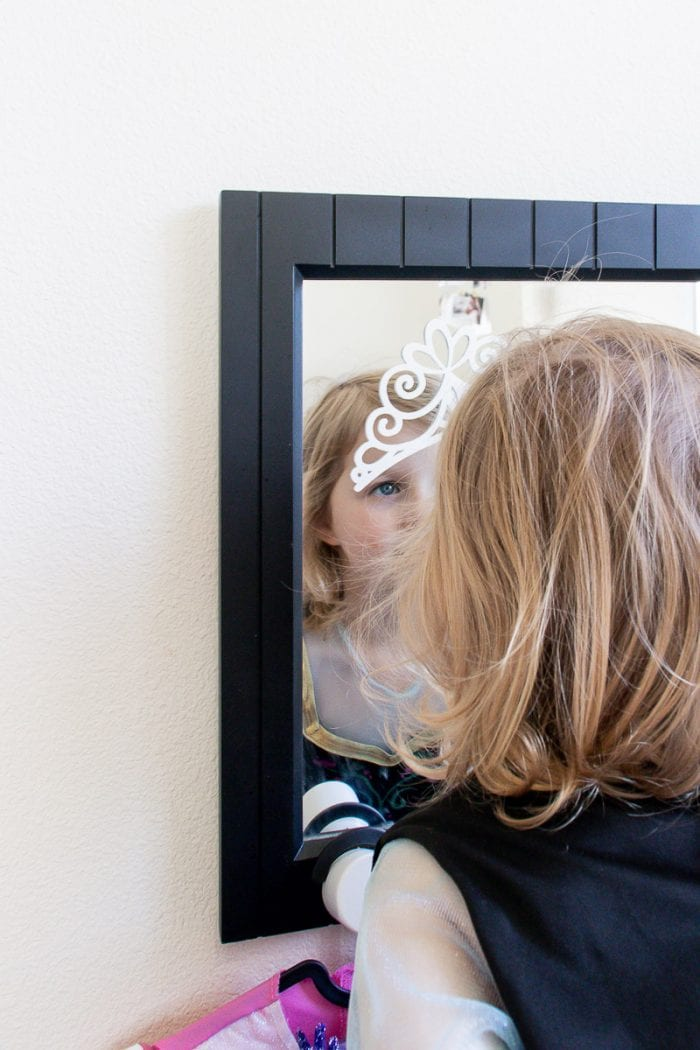 Image of little girl playing dress up looking in mirror