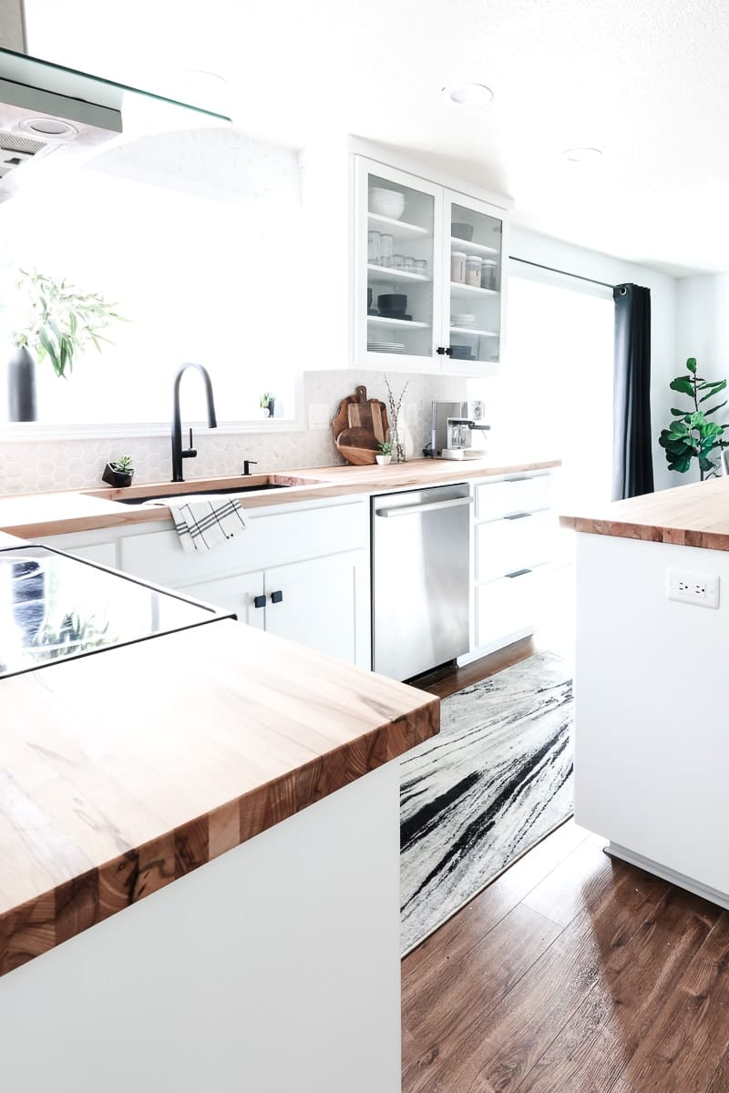 This modern kitchen makeover is filled with gorgeous black and white accents, hexagon tile backsplash, and many DIY projects. Check it out! #modernkitchen #renovation
