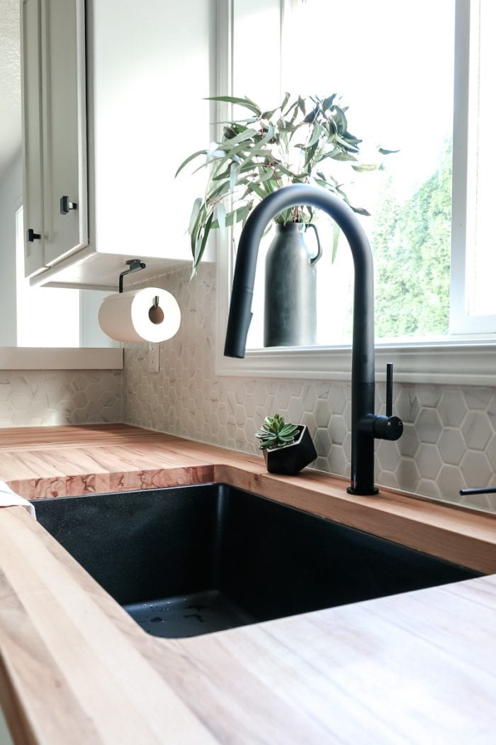 Side view of modern kitchen sink and black faucet