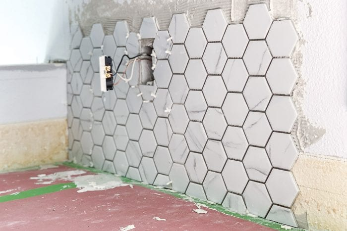 Installing tiles on the kitchen wall with FrogTape on the corners to protect the counter