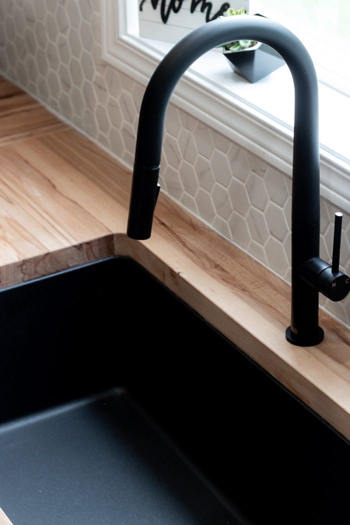 Closer view of the sink and the black faucet